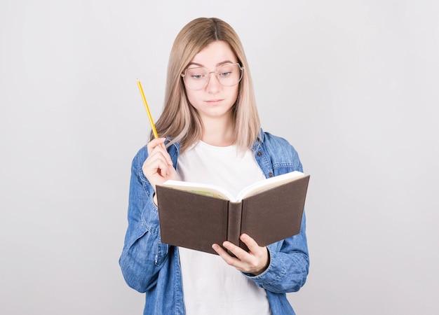 Uma escritora séria de cabelos loiros, óculos e camisa jeans, segurando um livro nas mãos e pensando no que escrever, na outra está um lápis. dia internacional dos escritores