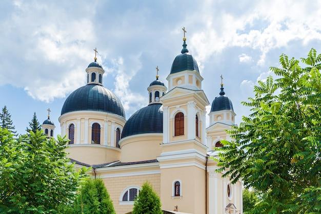 Uma escultura de um santo perto de uma igreja ortodoxa de pedra no fundo de um céu trovejante.
