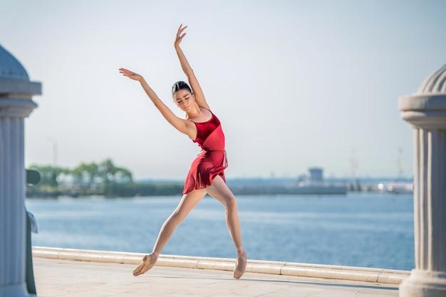 Uma esguia bailarina com sapatilhas de ponta e fantasia de noiva salta contra o fundo do mar