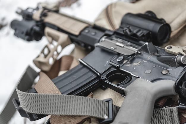 Uma espingarda de assalto encontra-se em uma pasta militar.