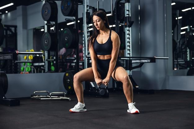 Uma esportista em uma roupa esportiva preta faz um agachamento profundo com um peso nas mãos