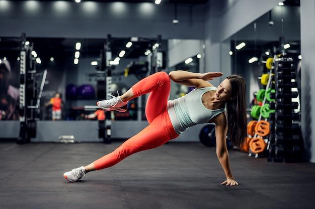 Uma esportista motivada faz uma prancha lateral para exercícios abdominais com uma mão e uma perna para cima na academia