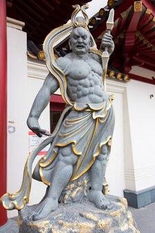 Uma estátua de deus chinês que guarda o templo e museu da relíquia do dente de buda em chinatown, em cingapura.