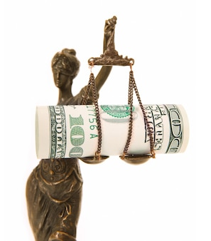 Uma estátua de themis com notas de dólar na escala como um símbolo de corrupção sobre o branco