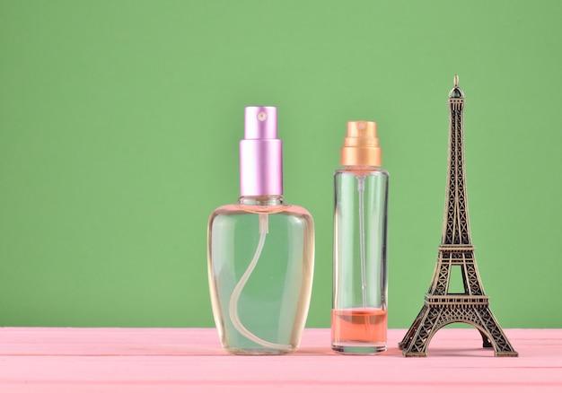 Uma estatueta da torre eiffel, frascos de perfume sobre fundo verde