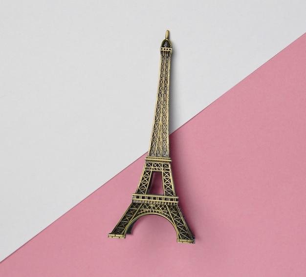 Uma estatueta de lembrança da torre eiffel em um pastel rosa branco.