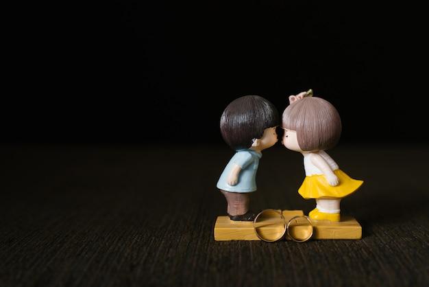 Uma estatueta de um cara e uma garota se beijando e alianças de casamento em um fundo marrom