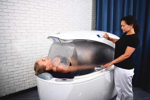 Uma esteticista ajusta os programas em uma cápsula de spa com uma cliente dentro dela recebendo tratamentos de spa para perda de peso, anticelulite, antienvelhecimento, massagem e alívio do estresse.
