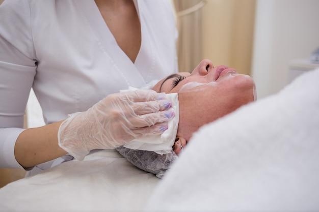 Uma esteticista de uniforme branco e boné limpa o rosto da cliente