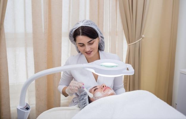 Uma esteticista em um uniforme branco faz uma máscara facial para uma cliente