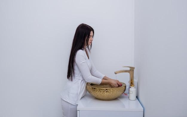 Uma esteticista em um uniforme branco levanta e lava as mãos