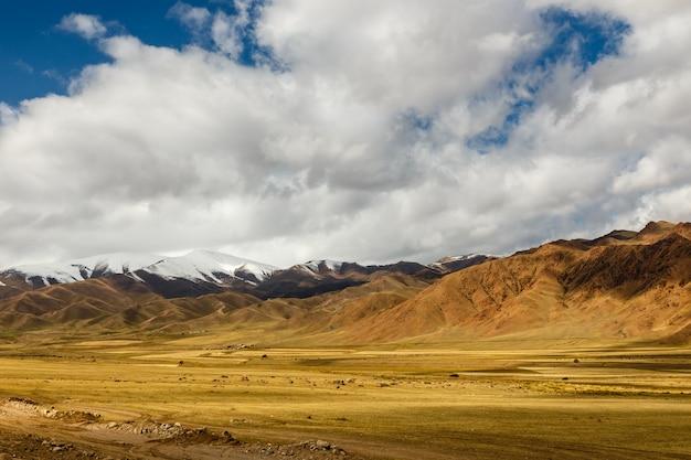 Uma estrada 367, passando na região de naryn, quirguistão, paisagem montanhosa perto da vila do distrito de uzunbulak kochkor
