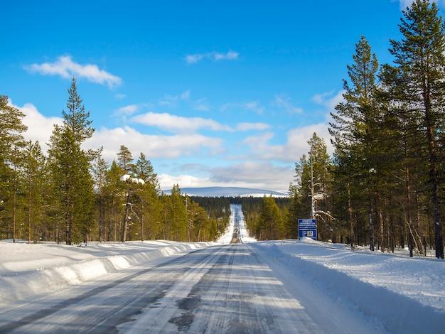 Uma estrada coberta de neve vazia no inverno