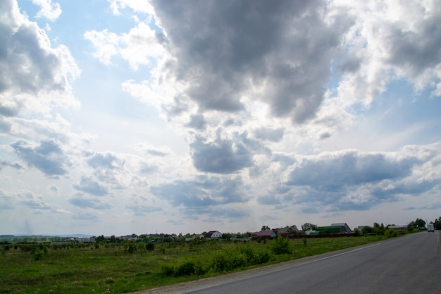 Uma estrada com um fundo de floresta e um céu azul com nuvens.