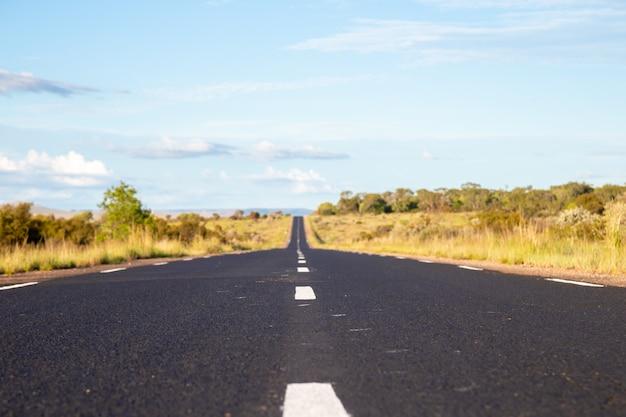 Uma estrada de asfalto reta com prados de ambos os lados