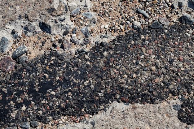 Uma estrada de asfalto ruim que foi reparada muitas vezes