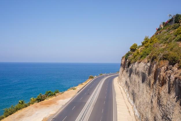 Uma estrada de asfalto vazia serpenteia ao longo da costa cênica de tirar o fôlego em um dia ensolarado de verão. uma foto espetacular de uma estrada costeira com vista para o céu azul e o calmo mar mediterrâneo.