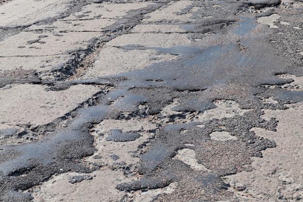 Uma estrada de má qualidade foi reparada muitas vezes, uma estrada ruim com buracos e fossos mal reparados
