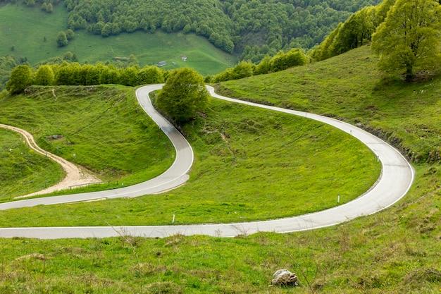 Uma estrada de montanha rodeada por vales e prados verdes.