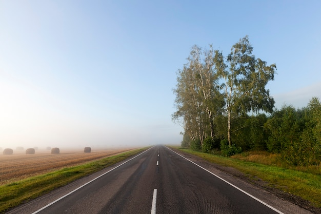 Uma estrada separada na estação da manhã, na frente de um grande nevoeiro, nas laterais da floresta e no campo agrícola