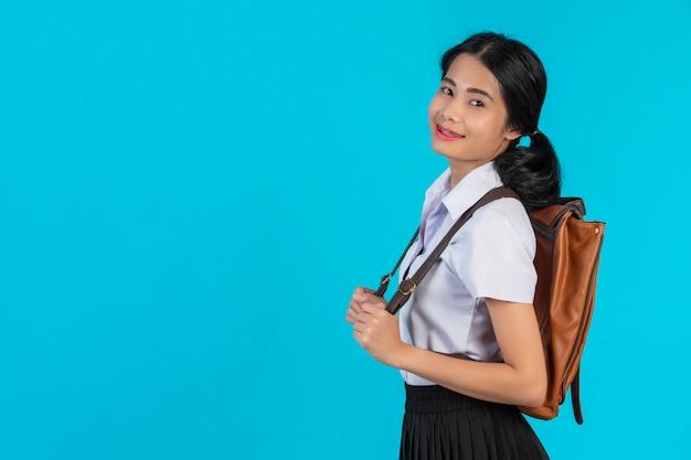 Uma estudante asiática espia sua bolsa de couro marrom em um azul.