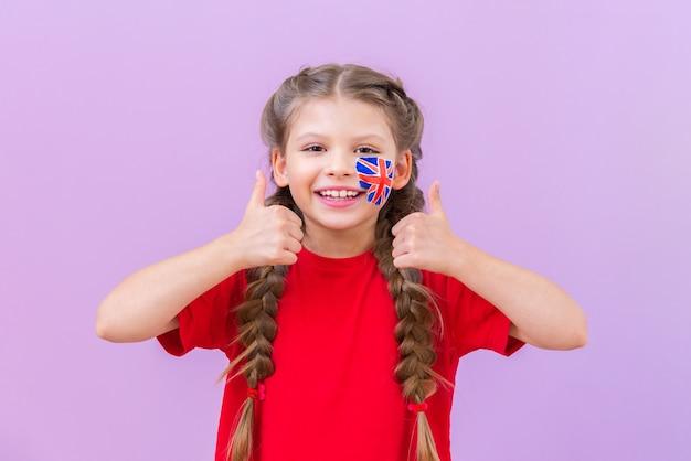 Uma estudante com uma bandeira britânica pintada na bochecha faz um sinal de positivo com o polegar.