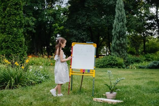 Uma estudante escreve aulas em um quadro negro e está envolvida em treinamento ao ar livre. de volta à escola, aprendendo durante a pandemia.