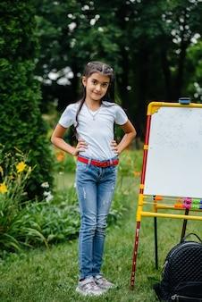 Uma estudante escreve aulas em um quadro negro e está envolvida em um treinamento ao ar livre