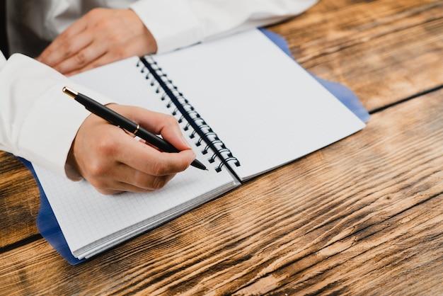 Uma estudante está sentada à mesa com um caderno e uma caneta.