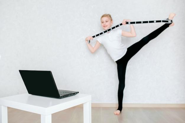 Uma estudante européia faz exercícios de alongamento com um elástico e assiste a vídeos on-line em um laptop. ginástica, coreografia. auto-isolamento, quarentena, educação on-line