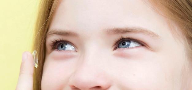 Uma estudante insere lentes de contato nos olhos.