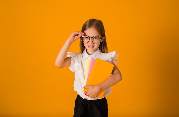 Uma estudante inteligente de uniforme e óculos segura um caderno em um fundo amarelo com um lugar para texto.