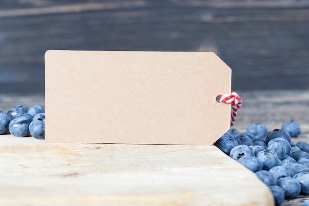 Uma etiqueta de papel junto com mirtilos suculentos e doces para escrever um preço ou outro recorde