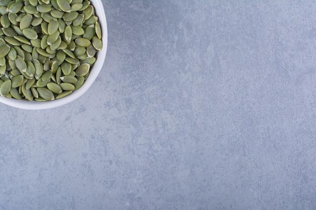 Uma exibição de sementes de abóbora em uma tigela na superfície de mármore