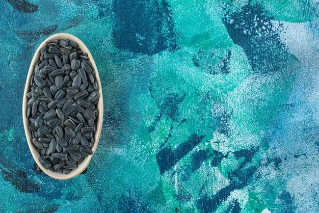Uma exibição de sementes de girassol com casca em uma tigela no mármore.