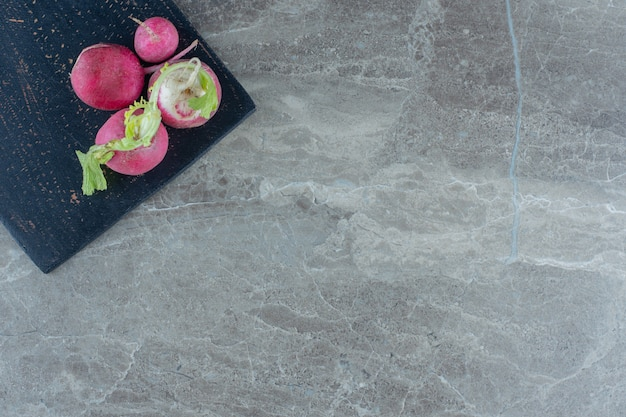 Uma exposição de rabanetes na tábua de cortar na mesa de mármore.