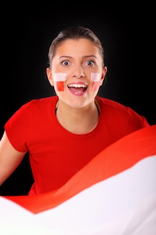 Uma fã polonesa feliz torcendo contra um fundo preto