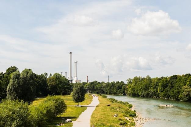 Uma fábrica com chaminés na margem do rio