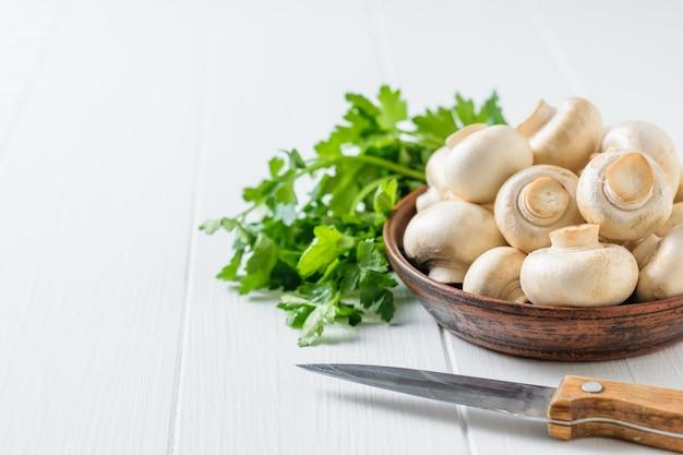 Uma faca ao lado de uma tigela de cogumelos e um monte de salsa em uma mesa branca