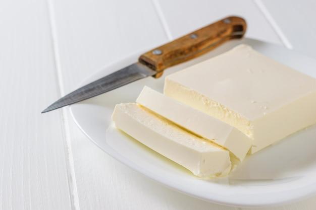 Uma faca com um cabo de madeira ao lado de uma fatia de queijo sérvio.
