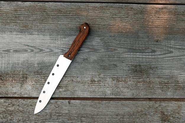 Uma faca com uma alça marrom fica sobre um cinza de madeira. copyspace.