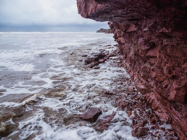 Uma falésia acima do mar com uma linha costeira estreita. ondas com espuma branca rolam no costão rochoso. costa de tersky, cape ship para a península de kola.