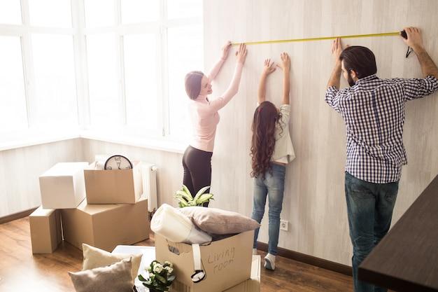 Uma família agradável e trabalhadora está trabalhando juntos. homem e mulher medem o comprimento da parede enquanto a filha tenta ajudá-los.