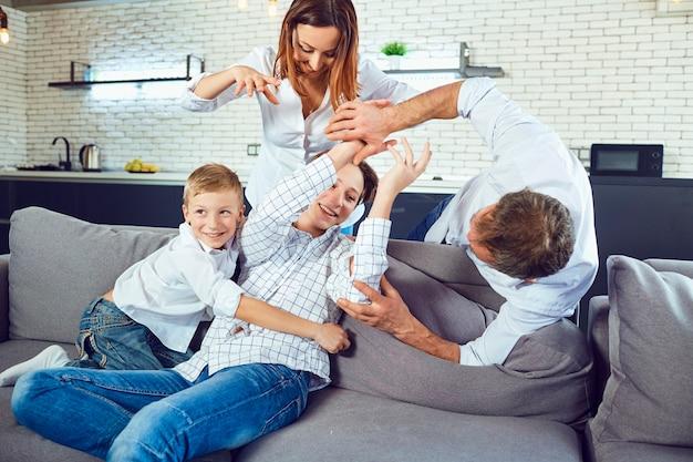 Uma família alegre está brincando no sofá da sala