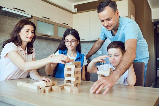 Uma família alegre joga jogos de tabuleiro em casa