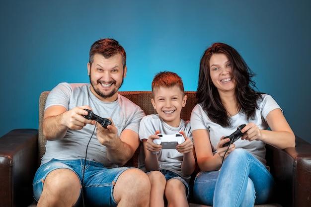 Uma família alegre, pai, mãe e filho jogam no console, videogame, reagem emocionalmente sentados no sofá. dia de folga, entretenimento, lazer, passam tempo juntos.