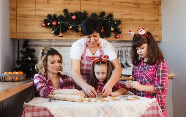Uma família amigável prepara biscoitos de gengibre na cozinha.