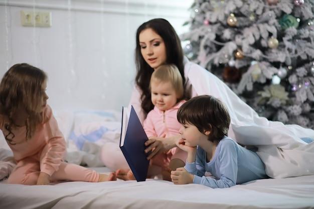 Uma família com crianças se divertindo na cama sob as cobertas durante as férias de natal.