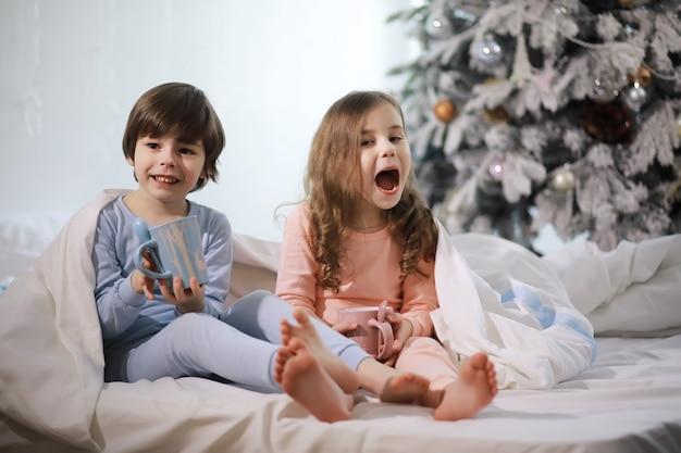 Uma família com crianças se divertindo na cama sob as cobertas durante as férias de natal