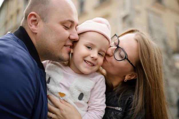 Uma família com uma filha está abraçando e se divertindo juntos.